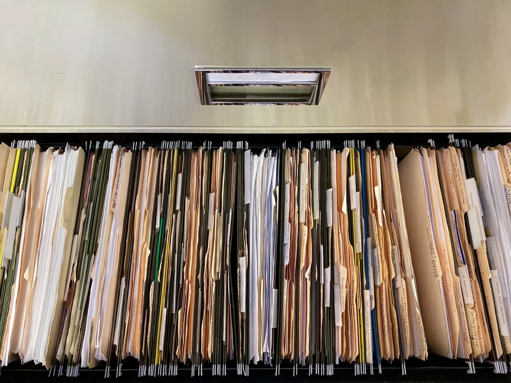 Filing cabinet filled with a bagilion files.