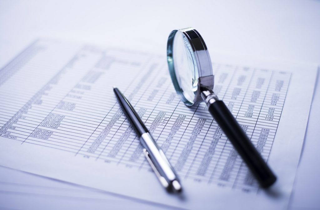 Money, pen, magnifying glass and the financial report