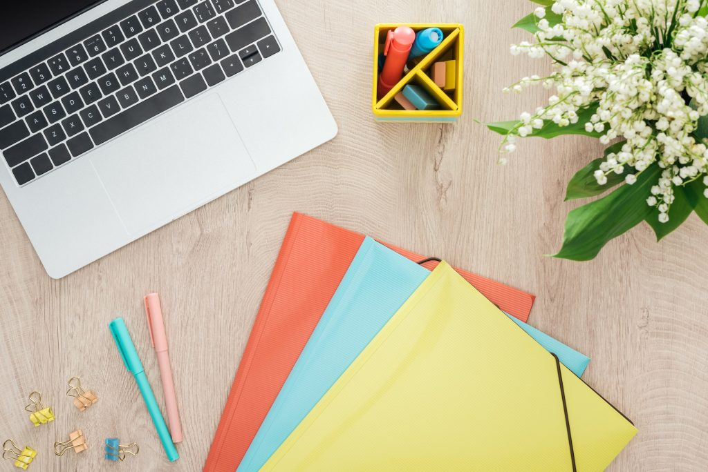 top view of folders, stationery, laptop and flowers on wooden table