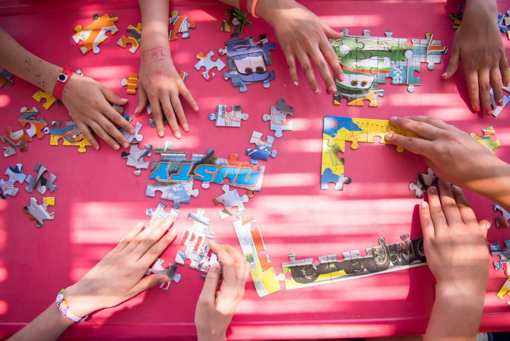 top view of kids hands playing with puzzles