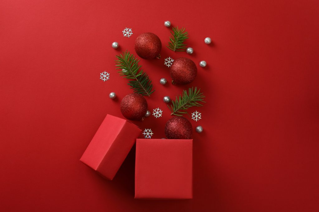 Gift box and Christmas baubles on red background