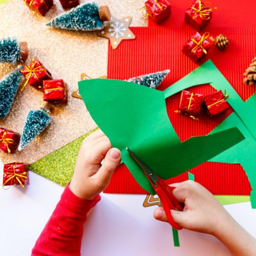 Kid playing with christmas crafts on white background.